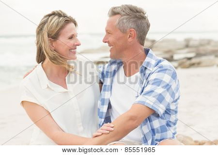 Casual couple smiling at each other at the beach