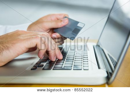 Man using laptop for online shopping in close up