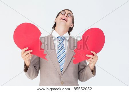 Geeky businessman crying and holding broken heart card on white background