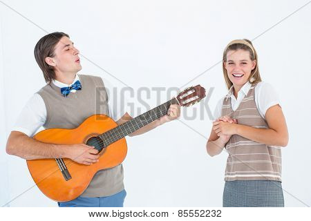 Geeky hipster serenading his girlfriend with guitar on white background
