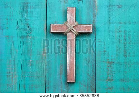 Rugged wooden cross hanging on distressed teal blue wood background