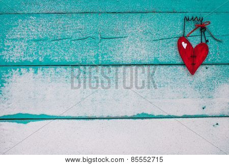 Red wooden heart hanging on sandy turquoise sign