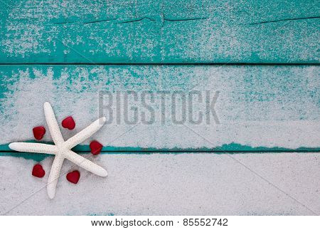 White starfish and red hearts on sandy teal blue sign
