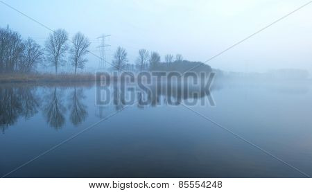 The shore of a foggy lake in winter at dawn