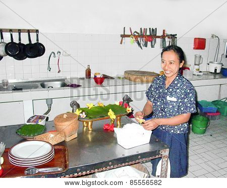 Woman Prepares In The Kitchen A Duck Balinese Style