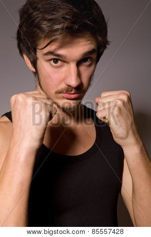 Studio portrait of a handsome young man showing his fists