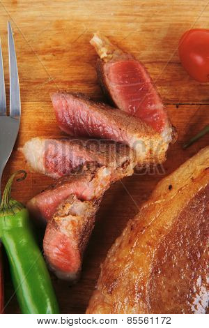 red meat steak sliced on wooden board with green hot pepper and cutlery isolated  over white background