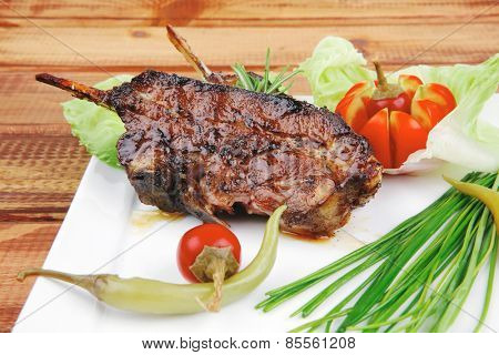 meat plate over wooden table: grilled ribs on white plate with red hot peppers, tomatoes and chives