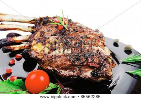 grilled baby ribs on black plate with cutlery
