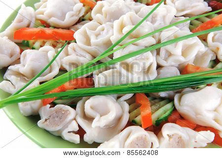 meat dumplings served on green plate with chives