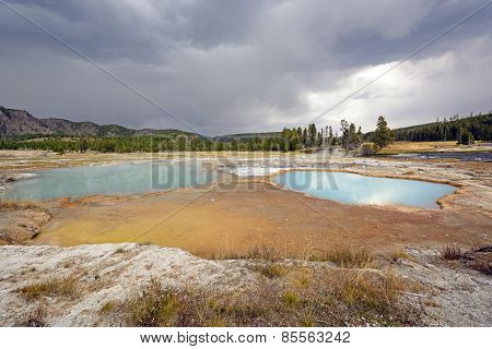 Storm Clouds Over A Colorful Thermal Pool