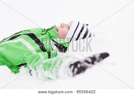 Young Child Relaxing Lying On The Fresh Snow