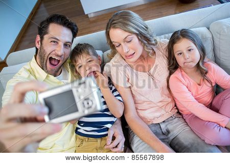 Happy family taking selfie on couch at home in the living room