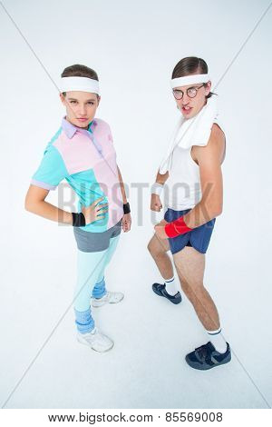 Geeky hipster couple posing in sportswear on white background