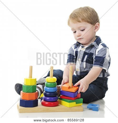 An adorable two year old unstacking a colorful wooden stack toy.  On a white background with plenty of space for your text on the left.