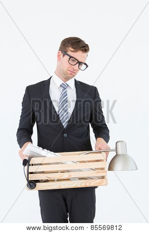 Sad geeky businessman holding box of his things on white background