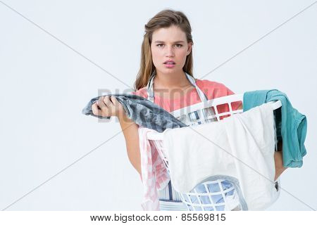 Hipster woman holding laundry basket on white background