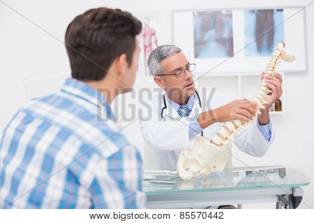 Doctor explaining anatomical spine to his patient in medical office