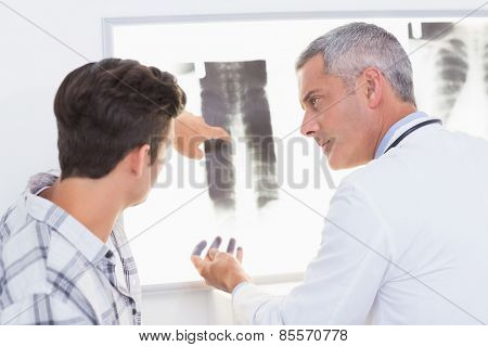 Doctor explaining X rays to his patient in medical office