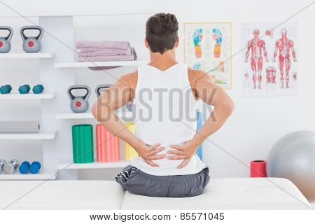 Young man suffering from back pain in medical office