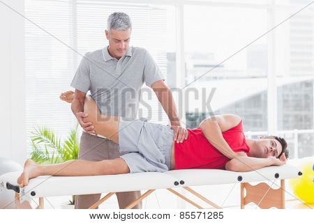 Physiotherapist doing leg massage to his patient in medical office