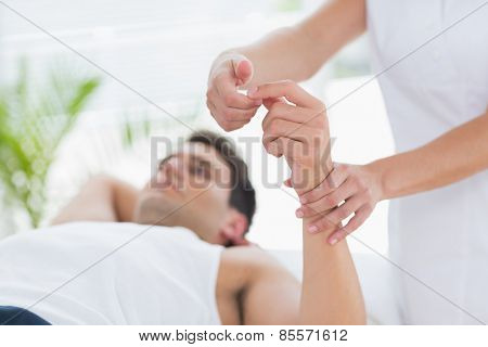 Physiotherapist examining her patient hand in medical office
