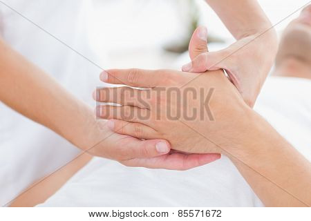 Physiotherapist doing hand massage in medical office