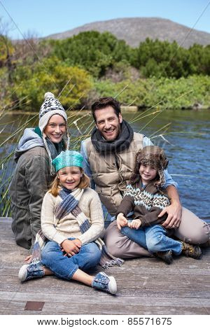 Happy casual family at a lake in the countryside