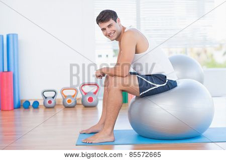 Smiling man sitting on exercise ball and looking at camera in fitness studio