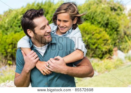 Father and son smiling at each other in the countryside