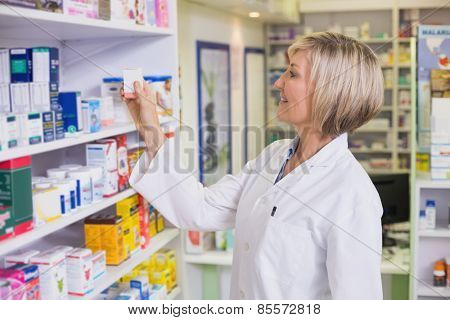 Pharmacist taking medicine from shelf at the hospital pharmacy