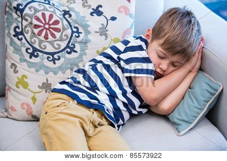 Little boy sleeping on the couch at home in the living room