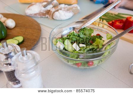 Family preparing salad at home in the kitchen