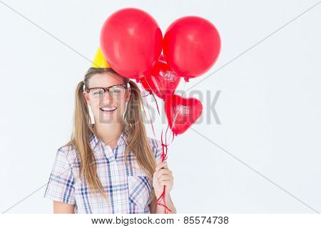 Geeky hipster smiling at camera and holding red balloons on white background