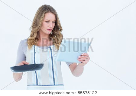 Concentrated woman holding frying pan and tablet pc on white background