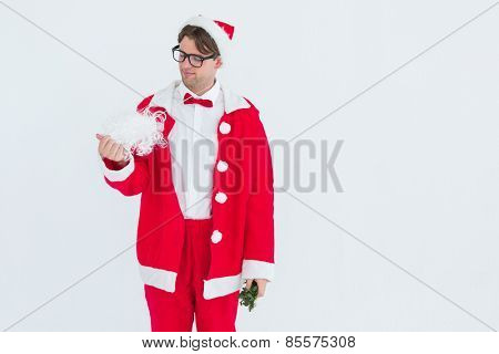 Geeky hipster in santa costume looking at beard on white background