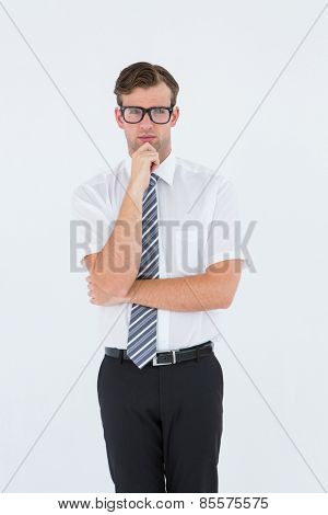 Serious geeky businessman thinking and holding his chin on white background