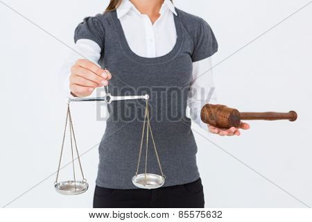 Woman holding a gavel and scales of justice on white background