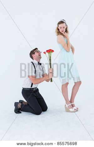 Geeky hipster begging his girlfriend taking roses on white background