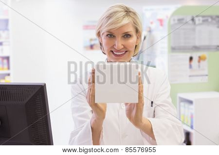 Pharmacist holding medicine box at pharmacy