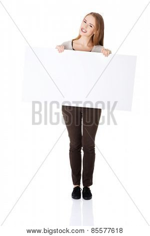 Full length happy woman holding an empty baner.