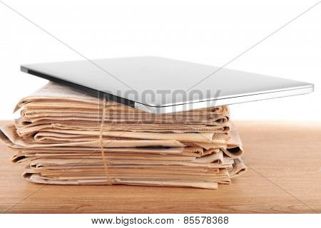 Laptop with stack of newspapers on table on white background