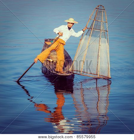 Vintage retro effect filtered hipster style image of Myanmar travel attraction landmark - traditional Burmese fisherman at Inle lake, Myanmar famous for their distinctive one legged rowing style