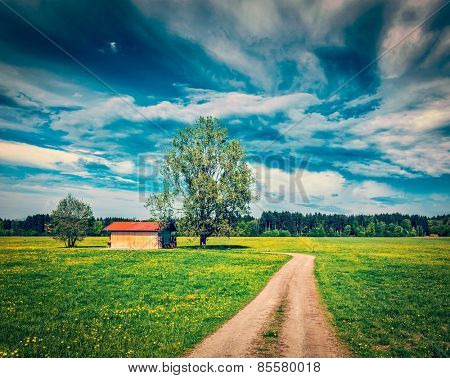 Vintage retro effect filtered hipster style image of rural road in summer meadow with wooden shed. Bavaria, Germany