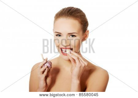 Portrait of nude woman eating garlic.