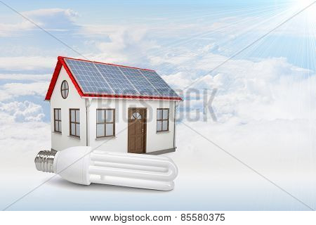 White house with red roof, solar panels in clouds. Background sun shines brightly