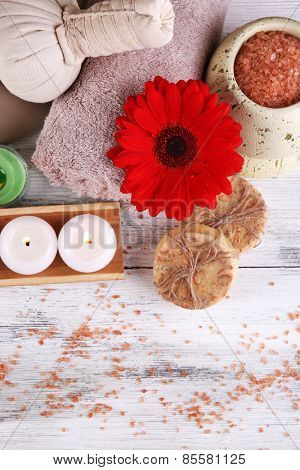 Composition of spa stones, sea salt and massage bags on wooden table, on light color background