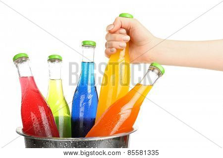 Female hand taking glass bottle of drink from metal bucket isolated on white