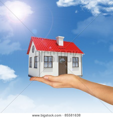White house in hand with red roof, chimney. Background sun shines brightly