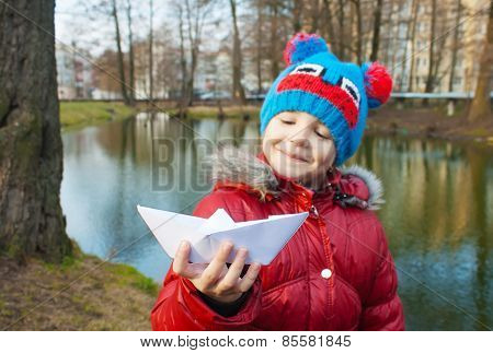 Little Girl Holding A Paper Boat Near The River